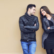Young happy cheerful couple standing near a wall and looking to — Stok fotoğraf