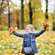 Little girl tossing leaves in autumn park — Stock Photo
