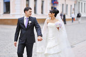 Bride and groom walking in an old town — Stock Photo