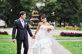 Bride and groom walking in a green park — Stock Photo