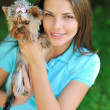 Young beautiful woman holding her puppy dog - outdoor portrait — Stock Photo