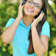 Beautiful young woman with headphones outdoors. Enjoying music — 图库照片