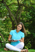 Girl with a book in a park — Stock Photo