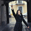 Beautiful young woman under an umbrella on a city street — ストック写真
