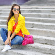 Stylish beautiful girl sitting on a stairs in colorful clothes w — Stock Photo