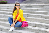 Stylish beautiful girl sitting on a stairs in colorful clothes w — Stockfoto