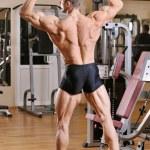 Bodybuilder posing at gym — Stock Photo