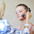 Young beautiful woman applying make-up by professional make-up a — Стоковая фотография