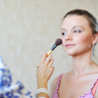 Young beautiful woman applying make-up by professional make-up a — Stock Photo