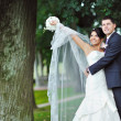 Young happy bride and groom enjoying freedom in a park — Стоковая фотография
