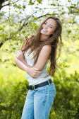 Pretty young smiling girl portrait in a green park — Stock fotografie