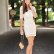 Young sensual lady in white dress with handbag — Stock Photo