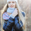 Stock Photo: Photo of pretty woman in winter cap and scarf looking at camera