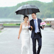 Happy bride and groom walking by the rain on their wedding day  — Stock Photo