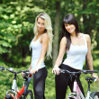 Portrait of pretty young women with bicycle in a park smiling -  — Stock Photo