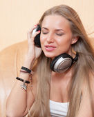 Young beautiful woman listening to music with headphones — Stock Photo
