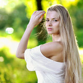 Young beautiful woman portrait in summer park — Stock Photo