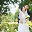 Photo: Beautiful kissing wedding couple. Outdoors portrait