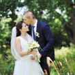 Beautiful kissing wedding couple. Outdoors portrait — Stockfoto