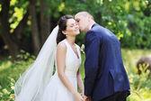 花嫁と花婿、公園での結婚式のカップルのキス — ストック写真