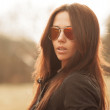 Outdoor fashion portrait of young brunette woman in sunglasses — Stock Photo