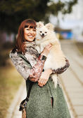 Young happy woman hold in hands small dog or puppy - outdoor por — Stock Photo