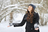Beautiful woman playing with snow in park — Stock Photo