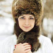 Young beautiful girl posing in a fur hat - close up — Stock Photo