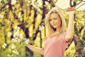 Outdoor portrait of young female in blooming tree in a summer pa — Stock Photo