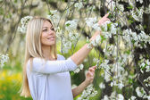 Beautiful young woman outdoors. Enjoy nature in blooming trees i — Stock Photo