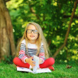 Cute little girl with a book in a green summer park — Stock Photo