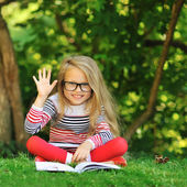 Sweet little girl with a book showing five - outdoors — Stock Photo