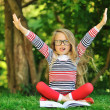Cute little girl with a book in a green summer park with hands r — Stock Photo