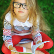 Angry and tired little girl with book in park — Stock Photo #39980087