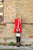 苗条的女孩站在一堵墙与韩寒穿着红色的肖像 — 图库照片
