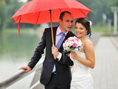 Cheerful married couple standing near a river — Stock Photo