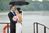 Happy young bride and groom in a rainy day — Stock Photo