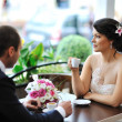 Bride and groom drinking coffee at an outdoor cafe — Stock Photo #40560739
