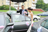 Young wedding couple getting in a car — Stock Photo