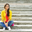 Stylish beautiful girl sitting on a stairs in colorful clothes — Stock Photo #41052751