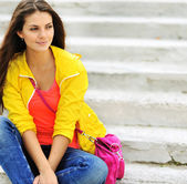 Stylish beautiful teen girl sitting on a stairs in colorful clot — Stock Photo