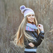 Outdoor portrait of sexy blonde girl in knitted clothes, smiling — Stock Photo