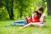 Beautiful romantic couple with tablet pc at summer green park — Stock Photo
