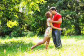 Young beautiful couple. Laugh and kiss. Summer green park  — Stock Photo