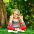 Cute little girl in with book in a park — Stock Photo