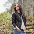 Beautiful young woman in sunglasses posing over nature backgroun — Stock Photo #42955961