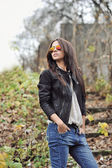 Beautiful young woman in sunglasses posing over nature backgroun — Stock Photo