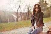 Beautiful woman in jacket and jeans sitting in a park wearing su — Foto Stock