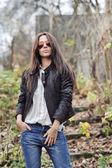 Fashion woman posing in a park wearing sunglasses  — Foto Stock