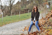 Attractive modern woman sitting in a autumn park — Stock Photo